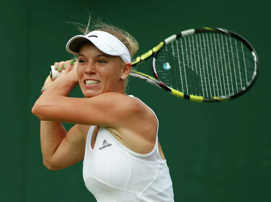 FILE - In this June 23, 2014 file photo, Caroline Wozniacki, of Denmark, watches a return to Shahar Peer of Israel during their first round match at the All England Lawn Tennis Championships in Wimbledon, London. Wozniacki plans to play a full tournament schedule this fall while fitting in time to train for the New York City Marathon. The former No. 1 player said Thursday, July 31, 2014,  that she long had wanted to do a marathon and decided before Wimbledon that she could pull it off this year.  (AP Photo/Alastair Grant, File) ORG XMIT: NY164 Photo: Alastair Grant / AP