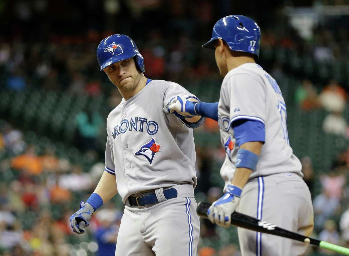 Toronto Blue Jays' Nolan Reimold, left, is congratulated by Ryan Goins, right, after hitting a home run against the Houston Astros during the ninth inning of a baseball game Thursday, July 31, 2014, in Houston. (AP Photo/David J. Phillip)