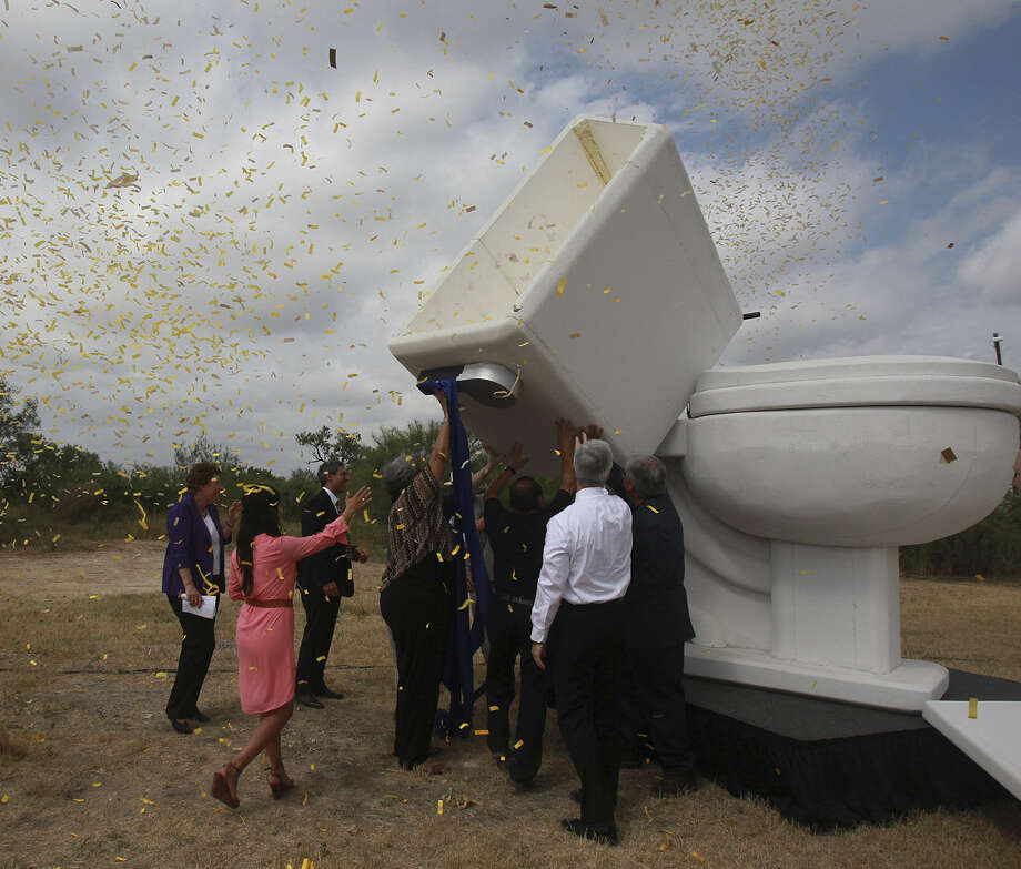 San Antonio Water System officials and dignitaries attempt to flush a giant faux toilet during a press conference on the completion of the Southwest Bexar Sewer Pipeline project. Photo: John Davenport / San Antonio Express-News / ©San Antonio Express-News/John Davenport