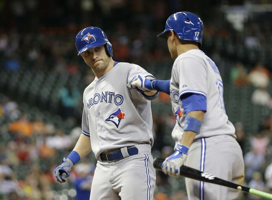 Toronto's Nolan Reimold is congratulated by Ryan Goins after hitting a ninth-inning home run. Photo: David J. Phillip, Associated Press
