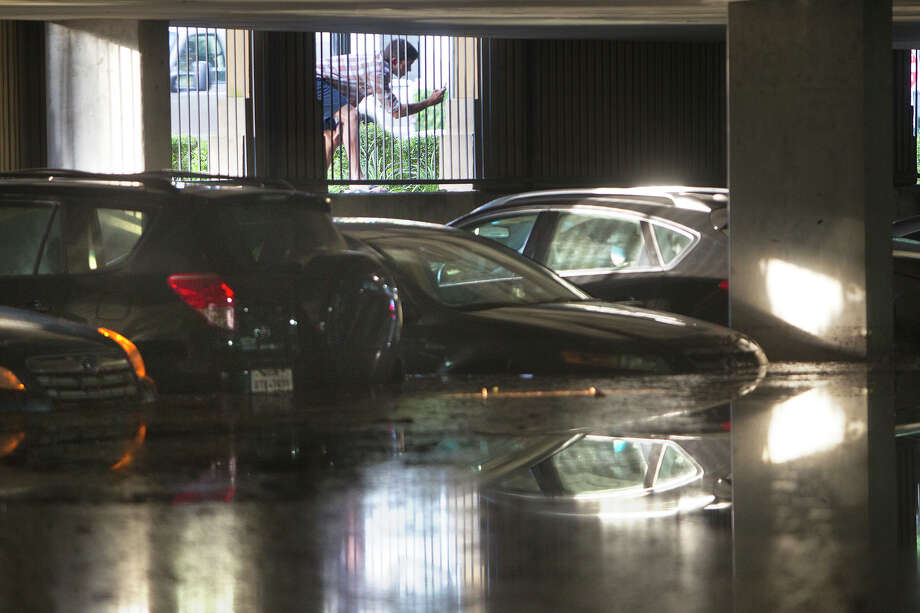 A man takes photos of cars as they sit in the Calais at Cortlandt Square apartment's parking garage after it flooded, Friday, Aug. 1, 2014, in Houston. Photo: Cody Duty, Houston Chronicle / © 2014 Houston Chronicle
