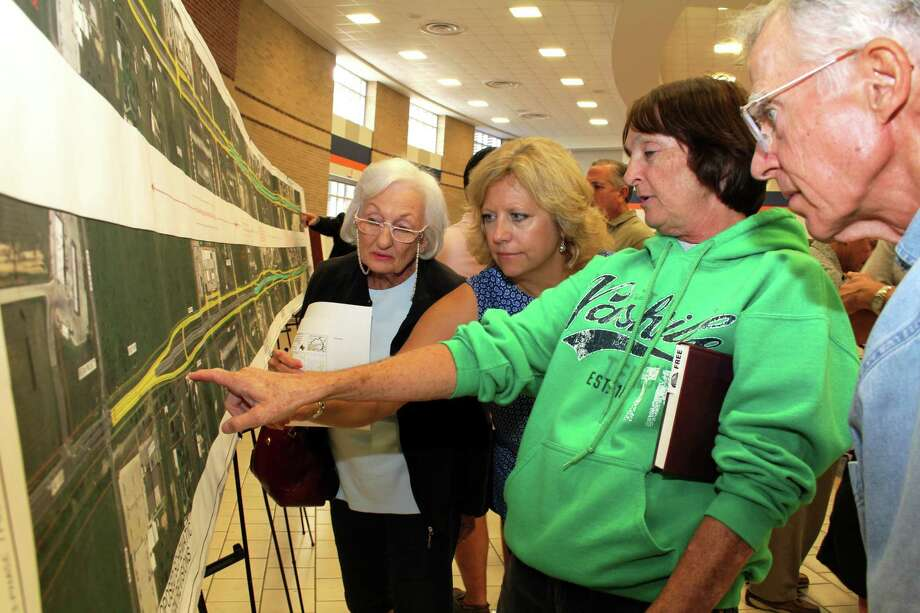Cindy Mixon points to the location of their residence at Covy Trails subdivision on a large mural at a public meeting at Cinco Ranch High School July 31 from 6-8 p.m.  From left, Cindy's mother, Rose Mixon and Ellen Stephenson, project manager for Jacobs who is handling the environmental for the project. Photo: Suzanne Rehak, For The Chronicle