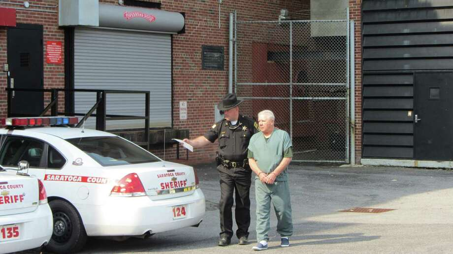 Charles Wilkinson, 68, is lead away from Saratoga County Court where he was arraigned on a second-degree murder charge. Wilkinson is accused of killing his wife, Kathleen Wilkinson, 65, and then living with her body for several days. (Bob Gardinier / Times Union)