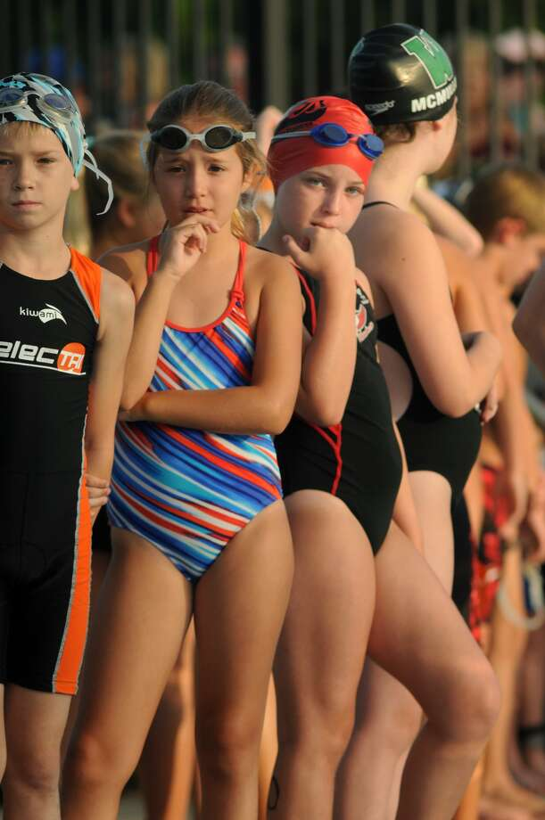 Competitors, including Layne Bale, 10, from left, of Conroe, Emily Madeley, 10, of The Woodlands, and Christiana Coker, 10, of Spring, line the pool deck as they wait for the start of the Greater Houston Kiwanis Kids Triathlon at the South Montgomery County YMCA on July 26. Photo: Jerry Baker, For The Chronicle