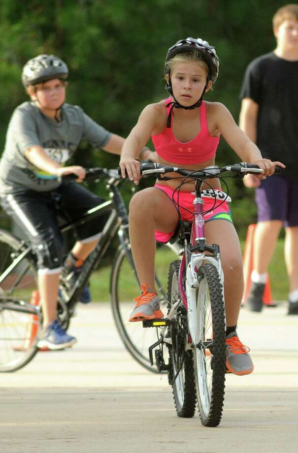 Ashley Hensley, 11, of The Wodlands, competes in the cycling portion of the Greater Houston Kiwanis Kids Triathlon at the South Montgomery County YMCA on July 26. Photo: Jerry Baker, For The Chronicle