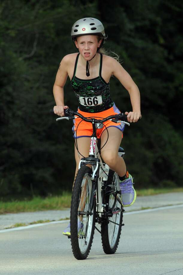Claire Winningham, 11, of The Woodlands, competes in the cycling portion of the Greater Houston Kiwanis Kids Triathlon at the South Montgomery County YMCA on July 26. Photo: Jerry Baker, For The Chronicle