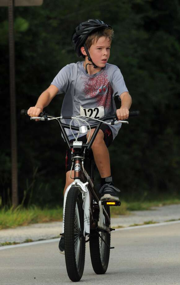 Andrew Kennemer, 10, of Montgomery, competes in the cycling portion of the Greater Houston Kiwanis Kids Triathlon at the South Montgomery County YMCA on July 26. Photo: Jerry Baker, For The Chronicle