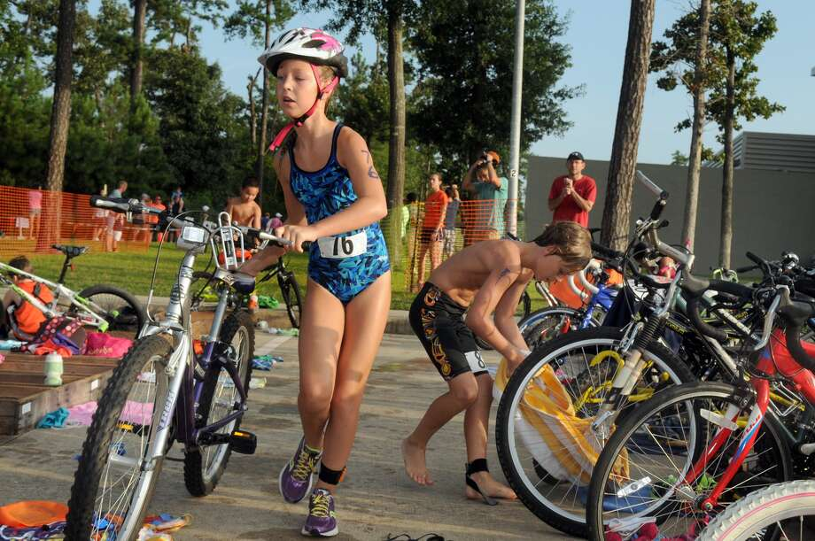 Cassidy Bernard, 9, from left, of Katy, and fellow competitor Joseph Marlow, 9, of The Woodlands, work through the staging area during the Greater Houston Kiwanis Kids Triathlon at the South Montgomery County YMCA on July 26. Photo: Jerry Baker, For The Chronicle