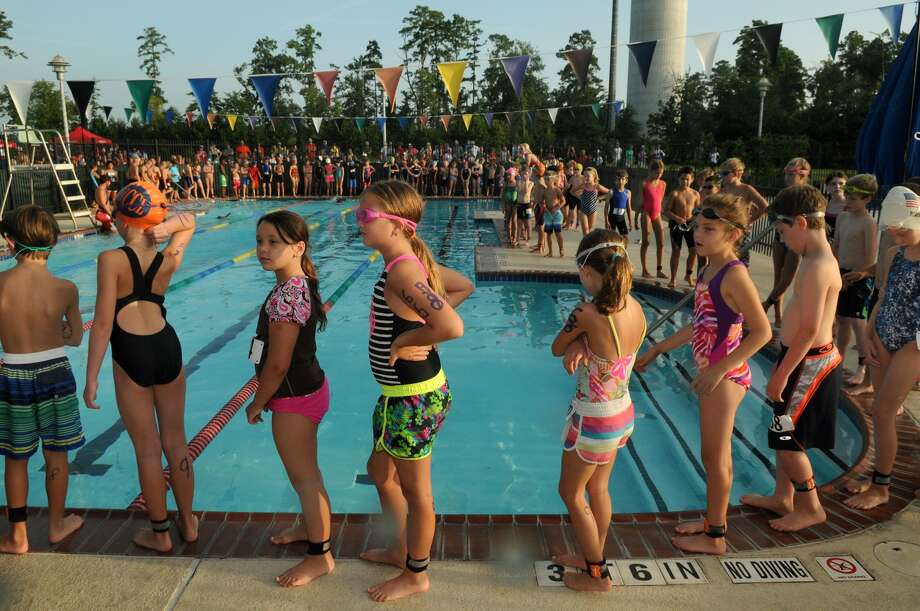 Competitors, including Hannah Oman, 9, center, line the pool deck as they wait for the start of the Greater Houston Kiwanis Kids Triathlon at the South Montgomery County YMCA on July 26. Photo: Jerry Baker, For The Chronicle