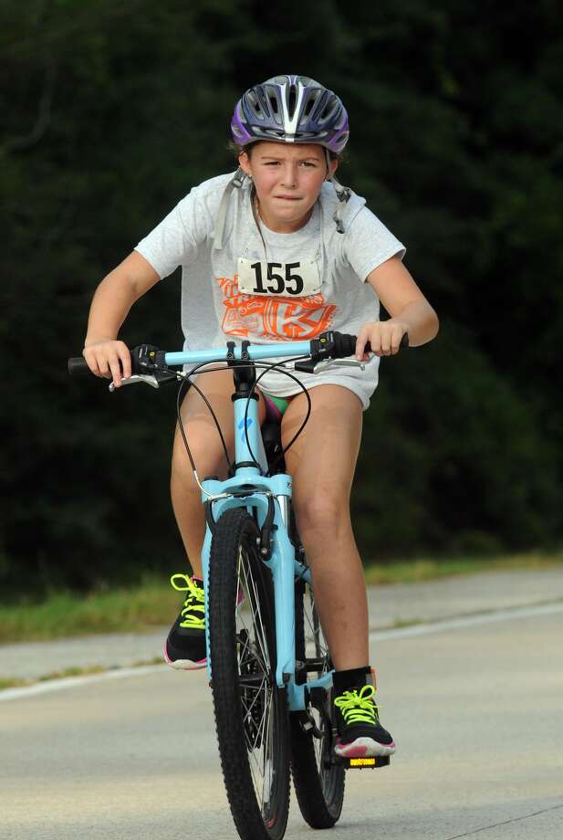 Ava Fuentes, 10, of The Woodlands and a 5th grader at Coulson Tough,  competes in the cycling portion of the Greater Houston Kiwanis Kids Triathlon at the South Montgomery County YMCA on July 26. Photo: Jerry Baker, For The Chronicle