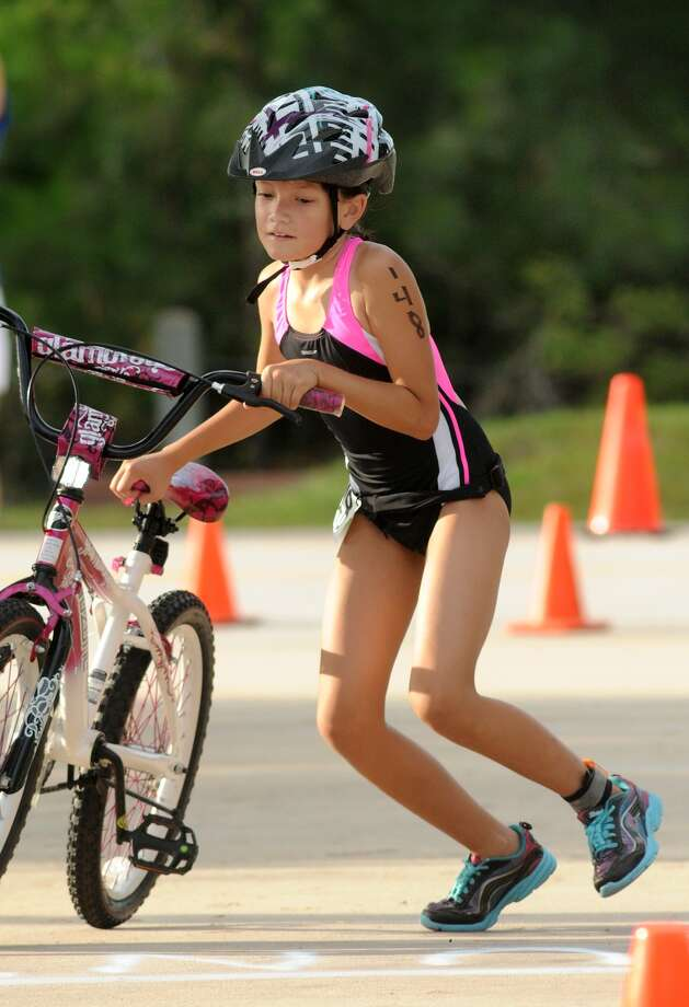 Riley Gonzales, 10, of Spring, works her way to the transition area during the Greater Houston Kiwanis Kids Triathlon at the South Montgomery County YMCA on July 26. Photo: Jerry Baker, For The Chronicle