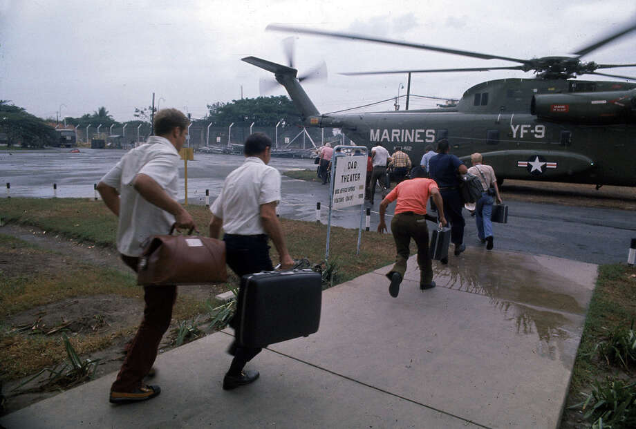 Fleeing Americans board a U.S. Marine helicopter at Tan Son Nhut Airbase in Saigon April 1975. American involvement in the Vietnam War came to an end when troops from communist North Vietnam invaded Saigon, the capital of the Republic of Vietnam in the South., 1975. Photo: Dirck Halstead, Getty Images / Hulton Archive