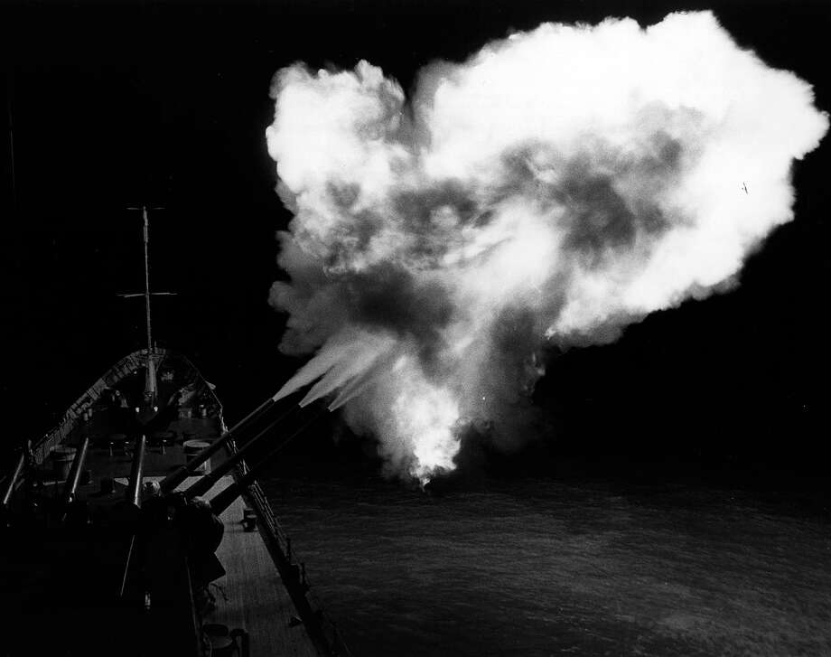 A flash from a triple salvo lights up the night as guns on the USS Canberra fire at military targets on the North Vietnamese coast, 1965. Photo: Hulton Archive, Getty Images / Hulton Archive