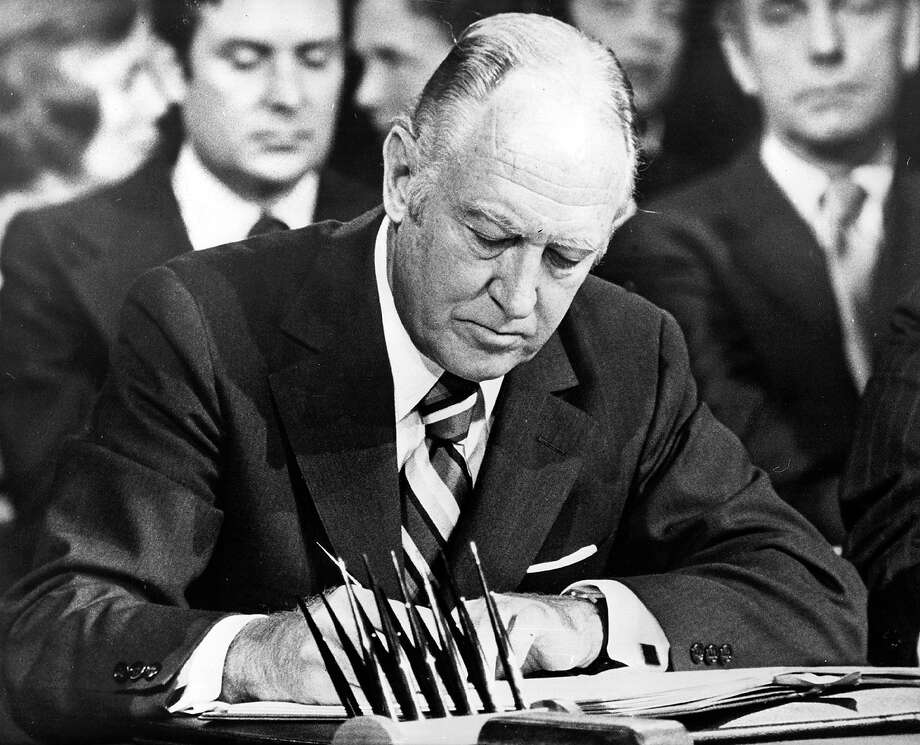United States Secretary of State William P. Rogers signing the Vietnam peace treaty in Paris, January 27, 1973. Photo: Keystone, Getty Images / Hulton Archive
