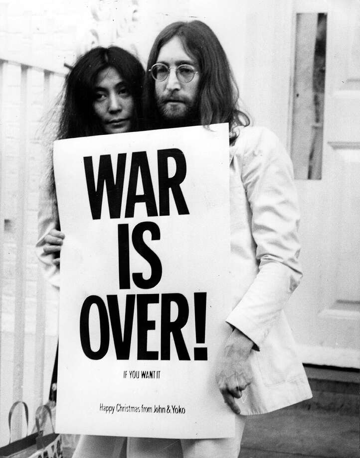 John Lennon and Yoko Ono pose on the steps of the Apple building in London, holding one of the posters that they distributed to the world's major cities as part of a peace campaign protesting against the Vietnam War. 'War Is Over, If You Want It,' 1969. Photo: Frank Barratt, Getty Images / Hulton Archive