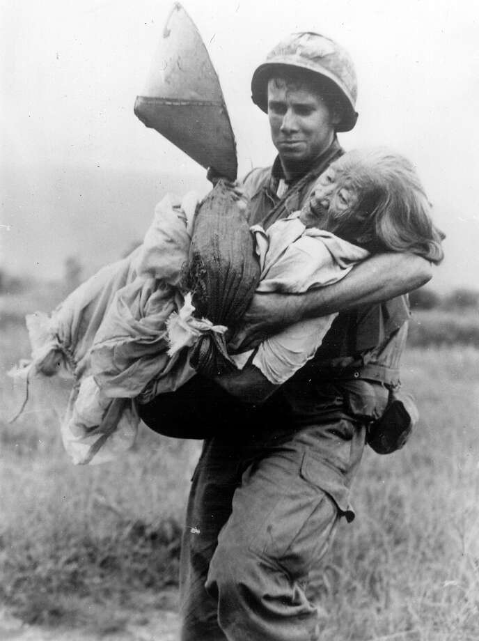A US Marine carries an elderly Vietnamese woman to a helicopter for evacuation to a refugee centre in a combat zone during the Vietnan War, 1970. Photo: Keystone, Getty Images / Hulton Archive