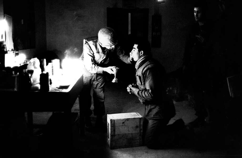 Marine chaplain Eli Tavesian giving communion to marine Louis A Loya, at Forward Command Post in Hue, Vietnam, 1968. Photo: Terry Fincher, Getty Images / Hulton Archive