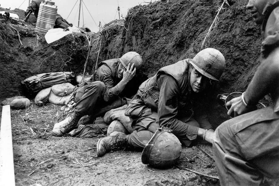 US troops take cover from the Vietcong in a trench on Hill Timothy, during the Vietnam War, 1968. Photo: Terry Fincher, Getty Images / Hulton Archive
