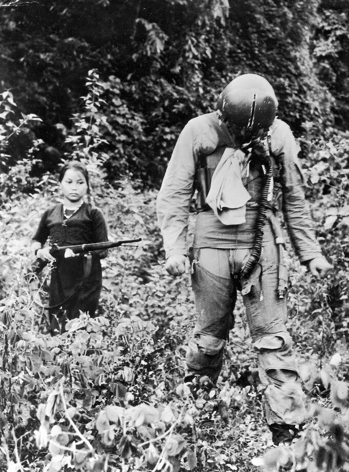 A North Vietnamese woman or girl points a rifle at American POW Gerald Santo Venanzi, a first lieutenant in the U.S. Air Force, as he walks in front of her through vegetation during the Vietnam War, North Vietnam, 1967 Photo: Hulton Archive, Getty Images / Archive Photos