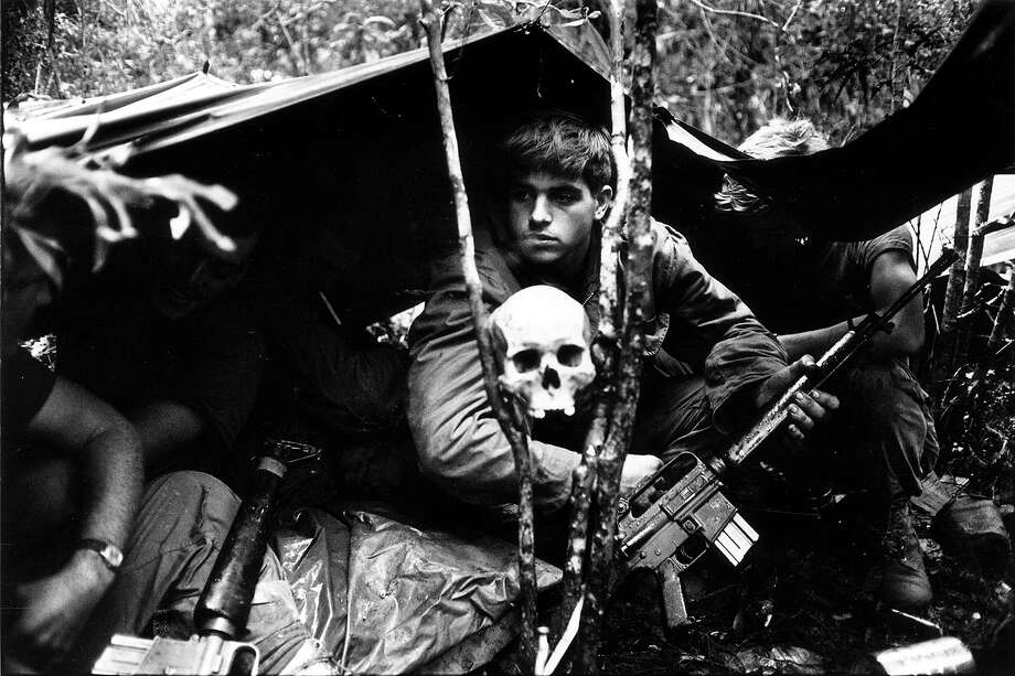A human skull keeps watch over US soldiers encamped in the Vietnamese jungle during the Vietnam War, 1968. Photo: Terry Fincher, Getty Images / Hulton Archive