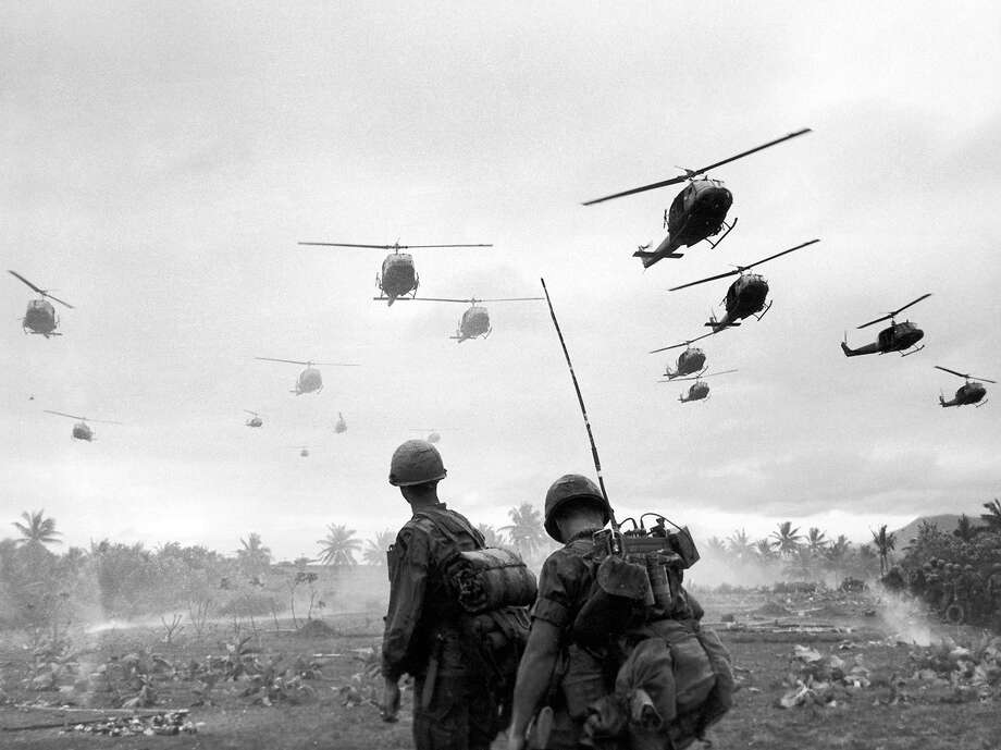 The second wave of combat helicopters of the 1st Air Cavalry Division fly over an RTO and his commander on an isolated landing zone during Operation Pershing, a search and destroy mission on the Bong Son Plain and An Lao Valley of South Vietnam, during the Vietnam War, 1967. Photo: Patrick Christain, Getty Images / Hulton Archive