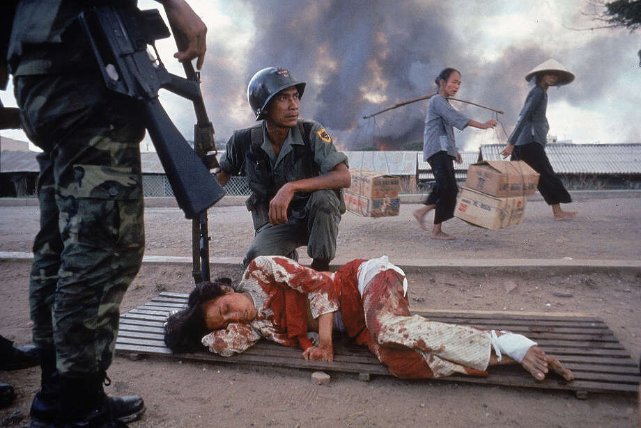 A South Vietnamese soldier crouched next to badly bleeding woman while awaiting medical aid during an attack by the Viet Cong, 1968. Photo: Larry Burrows, The LIFE Picture Collection/Gett / Time Life Pictures