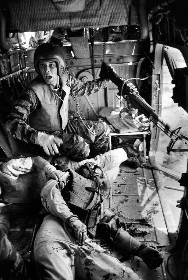 Helicopter crew chief James C. Farley (L) w. jammed machine gun shouting to crew as wounded pilot Lt. James E. Magel (1940 - 1965) lies dying beside him, Vietnam, March 31, 1965. Photo: Larry Burrows, The LIFE Picture Collection/Gett / Time Life Pictures