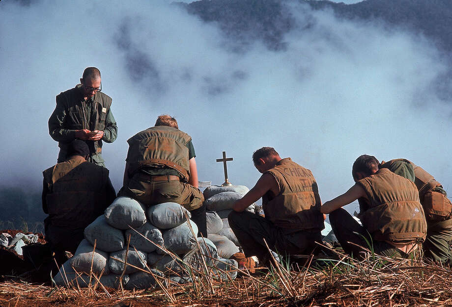 Chaplin Ray Stubbe leads a group of Marines in prayer near their sandbagged position along the perimeter of their base, Khe Sanh, Vietnam, early 1968. Photo: Dick Swanson, The LIFE Images Collection/Getty / Time Life Pictures