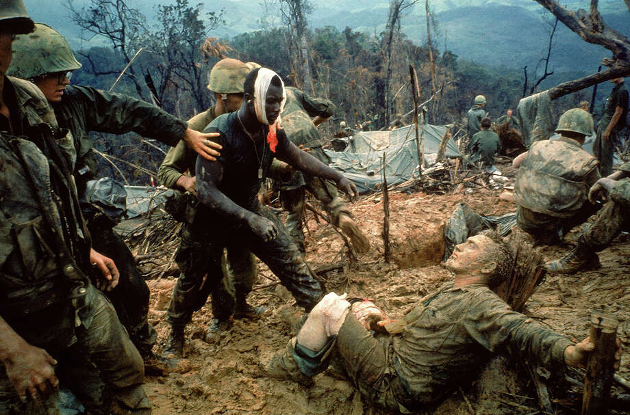 Wounded Marine Gunnery Sgt. Jeremiah Purdie (C) being led past stricken comrade after fierce firefight for control of Hill 484 south of the DMZ, 1966. Photo: Larry Burrows, The LIFE Picture Collection/Gett / Time & Life Pictures