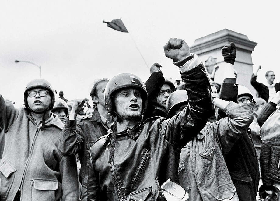 Young men raise their fists and chant slogans during the 'Days of Rage' demonstrations organized by the Weathermen to protest the Chicago Seven trial and 'to bring the war home,' Chicago, October 11, 1969. The plinth in the background held a statue dedicated to the policemen killed during the Haymarket Riot until the Weathermen bombed it on October 8th. It was rebuilt and bombed again in 1970 then rebuilt and moved indoors to the police academy. Photo: David Fenton, Getty Images / 2006 Getty Images