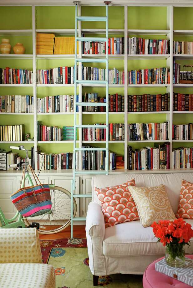 "Benjamin Moore's Tasty Apple brightens up the bookcase in the library, which is more feminine than the rest of the house. ""I change the pillows out a couple of times are year, and it iltereally creats the effect of a new room,"" says Kanter. Photo: Russell Yip, Staff / ONLINE_YES"