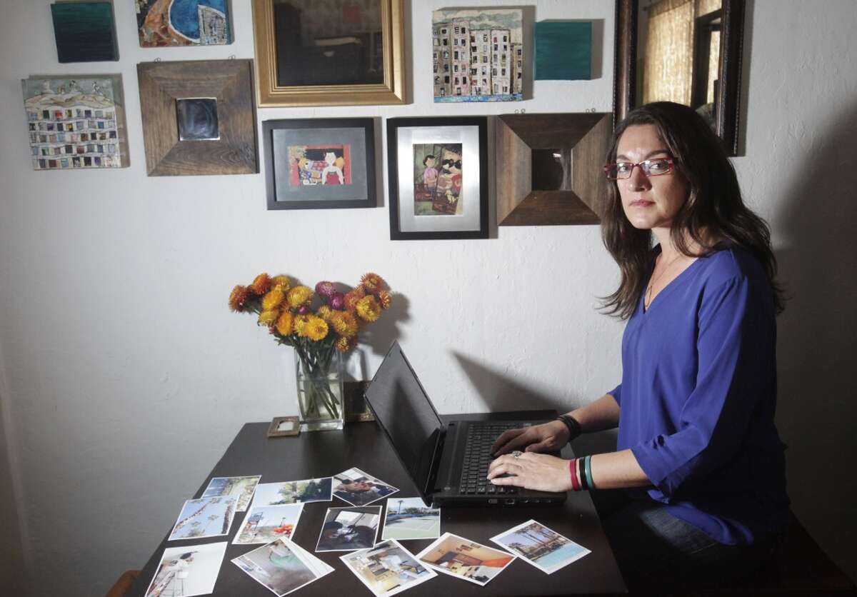 Cory Tschogl sits in her S.F. apartment, surrounded by photos of the Palm Springs home she has been renting out on Airbnb. Tschogl said two men were squatting at her condo, refusing to leave.