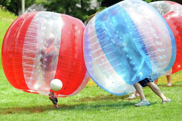 Times Union writer Amy Biancolli, left, kicks the ball during a game of Bubble Soccer against the JMU 4 Kids Xtreme Camp team on Wednesday, July 30, 2014, at the Academy of the Holy Names in Albany, N.Y. (Cindy Schultz / Times Union) Photo: Cindy Schultz / 00027971A