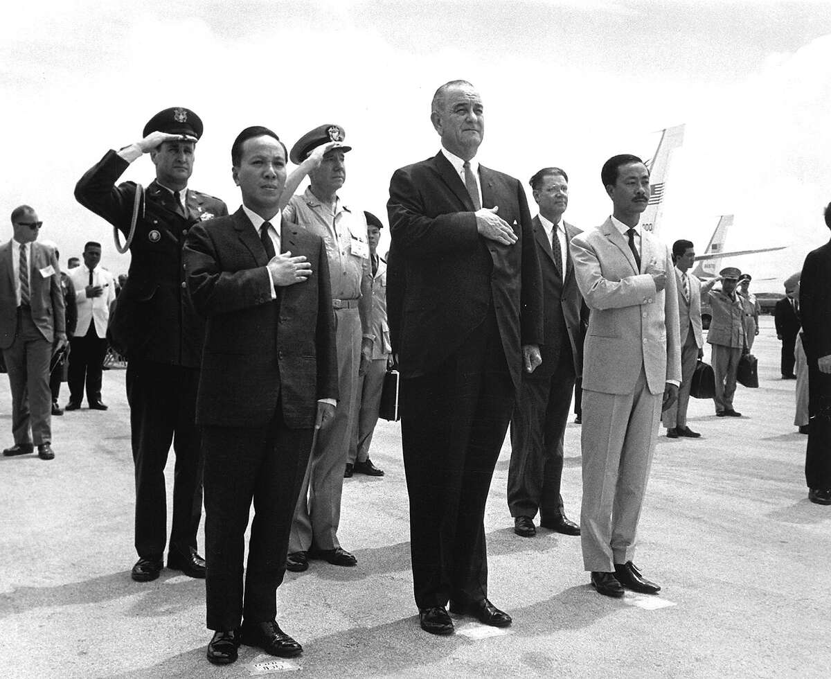 Front row, from left to right, Chairman Nguyen Van Thieu, President Lyndon B. Johnson and Prime Minister Nguyen Cao Ky salute during the playing of the American and Vietnamese national anthems at Guam's International Airport, Agana, March 20, 1967. Johnson gathered his top domestic officials with South Vietnamese leaders for a Guam Island conference to discuss the ongoing war in Vietnam.