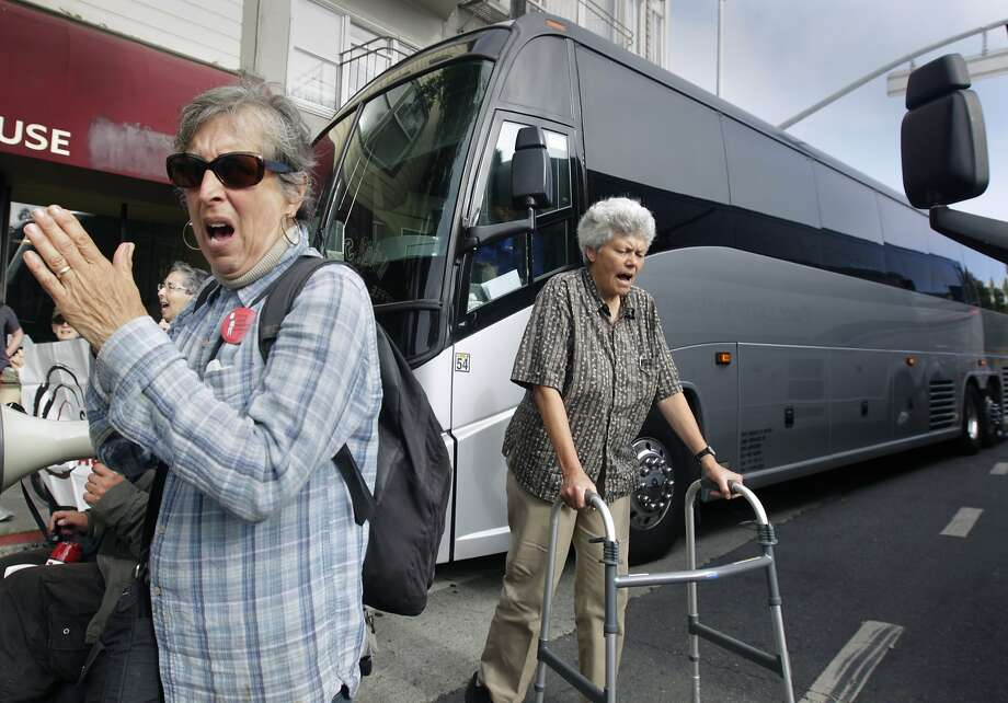 A group of seniors and disabled residents, protesting problems they blame on the tech industry and its workers, block two shuttle buses picking up tech employees at 24th and Valencia streets. Photo: Paul Chinn, The Chronicle