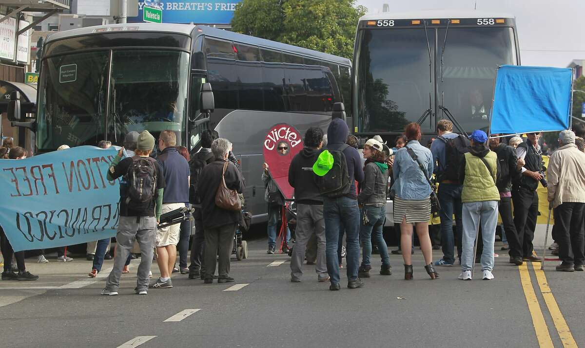 Protesters block two shuttle buses picking up tech employess at 24th and Valencia streets in San Francisco in August 2014.