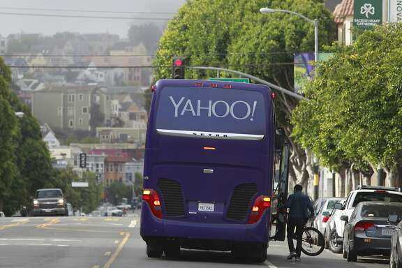 A Yahoo shuttle bus picks up employees in the middle of the block to avoid a group of seniors and disabled residents that blocked two other buses at 24th and Valencia streets in San Francisco, Calif. on Friday, Aug. 1, 2014. The group was protesting against the tech industry and workers.