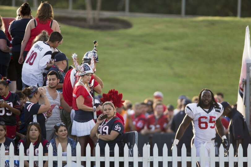 Fans watch Texans players like linebacker Jason Ankrah (65) arrive for practice.