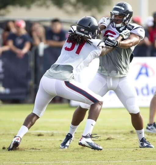 Texans linebackers Paul Hazel (51) and Chris McAllister (64) go through a pass rush drill.