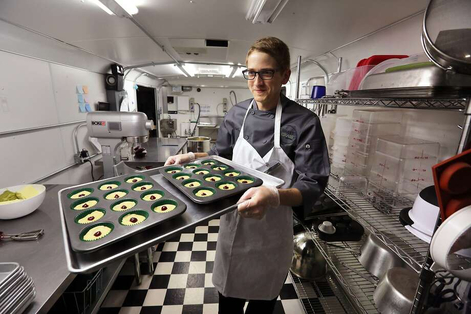 FILE - In this June 19, 2014, file photo, chef Alex Tretter carries a tray of cannabis-infused peanut butter and jelly cups to the oven for baking at Sweet Grass Kitchen, a well-established Denver-based gourmet marijuana edibles bakery which sells its confections to retail outlets throughout the state. Colorado marijuana regulators have drafted an emergency rule aimed at making it easier for new marijuana users to tell how much pot they are eating. (AP Photo/Brennan Linsley, File) Photo: Brennan Linsley, Associated Press