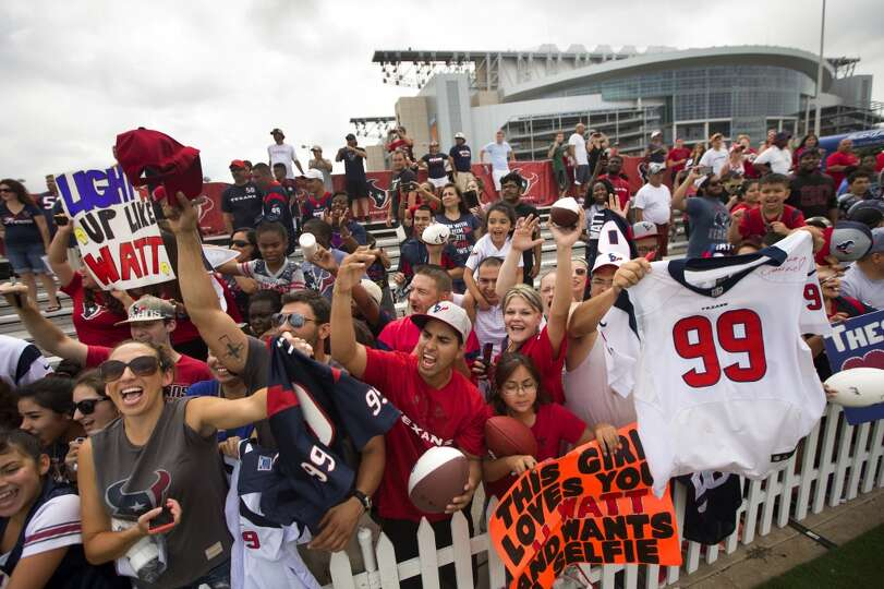 Texans fans yell as they seek autographs.