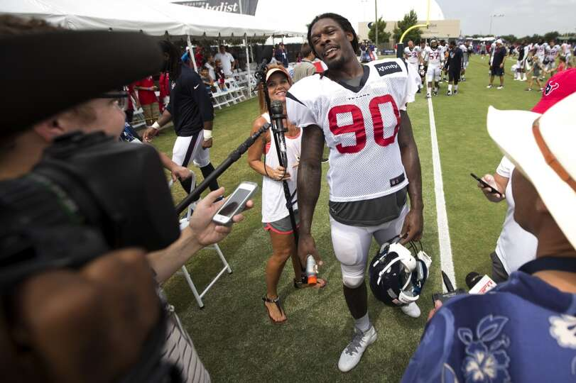 Texans linebacker Jadeveon Clowney smiles as he walks toward an interview with the media.