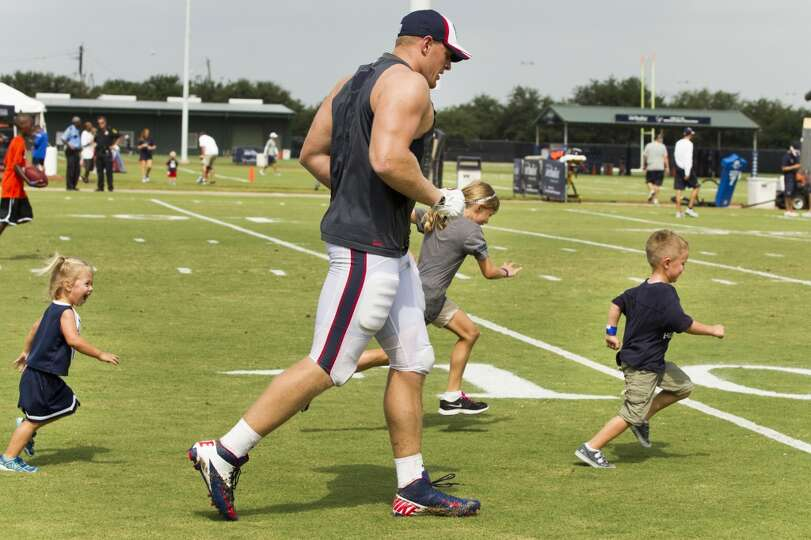 Texans defensive end J.J. Watt, left, runs downfield with Grace Colman, Sarah Colman and Matthew Col