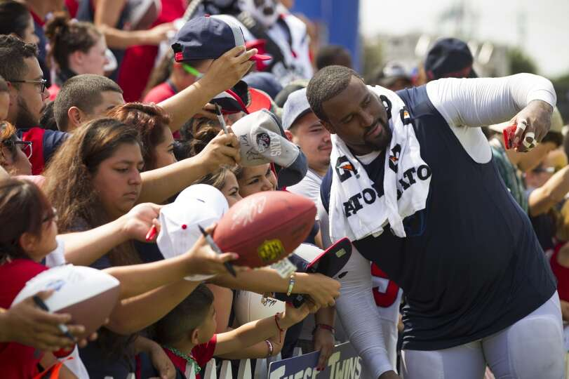 Texans tackle Duane Brown takes a photo of himself with a fan on after practice.