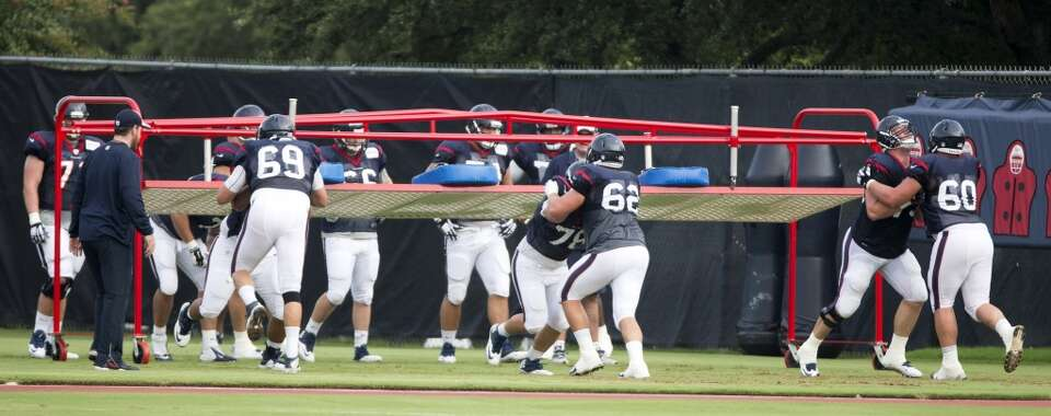 Texans offensive linemen run blocking drills.