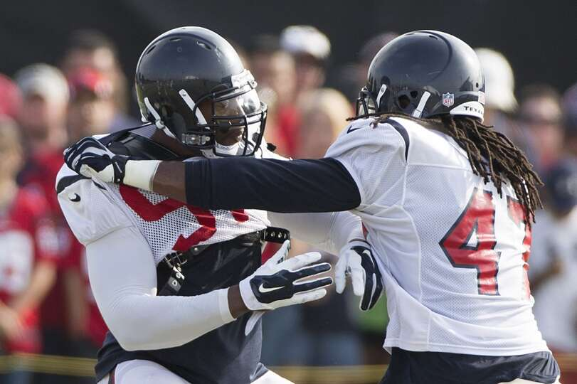 Texans linebackers Lawrence Sidbury (91) and Quentin Groves (47) run a pass rush drill.