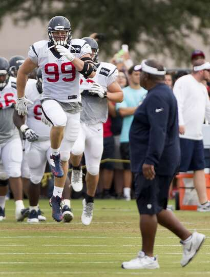 Texans defensive end J.J. Watt (99) jumps while warming up as defensive coordinator Romeo Crennel wa