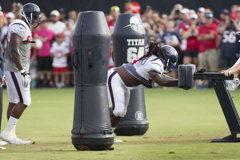 Texans defensive tackle Ricardo Mathews hits a blocking sled.