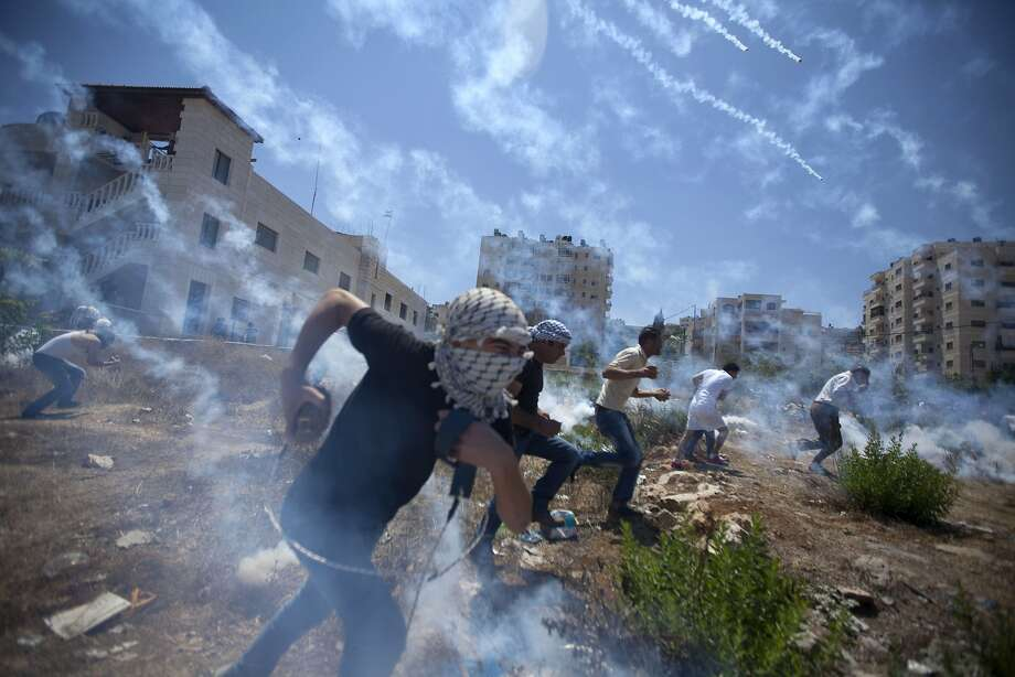 Palestinians run for cover during clashes with Israeli soldiers following a protest against the war in the Gaza Strip, outside Ofer, an Israeli military prison near the West Bank city of Ramallah, Friday, Aug. 1, 2014. (AP Photo/Majdi Mohammed) Photo: Majdi Mohammed, Associated Press