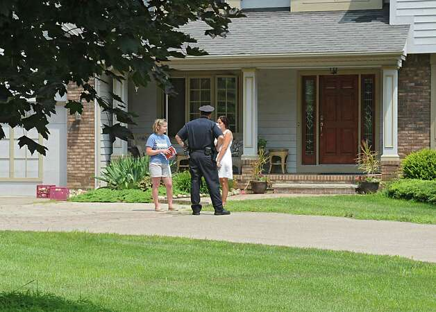 Police talk to neighbors as they investigate a body that was found at 63 Union Ave. home on Friday, Aug. 1, 2014 in Delmar, N.Y. This house is directly across from number 63. (Lori Van Buren / Times Union) Photo: Lori Van Buren / 00028036A